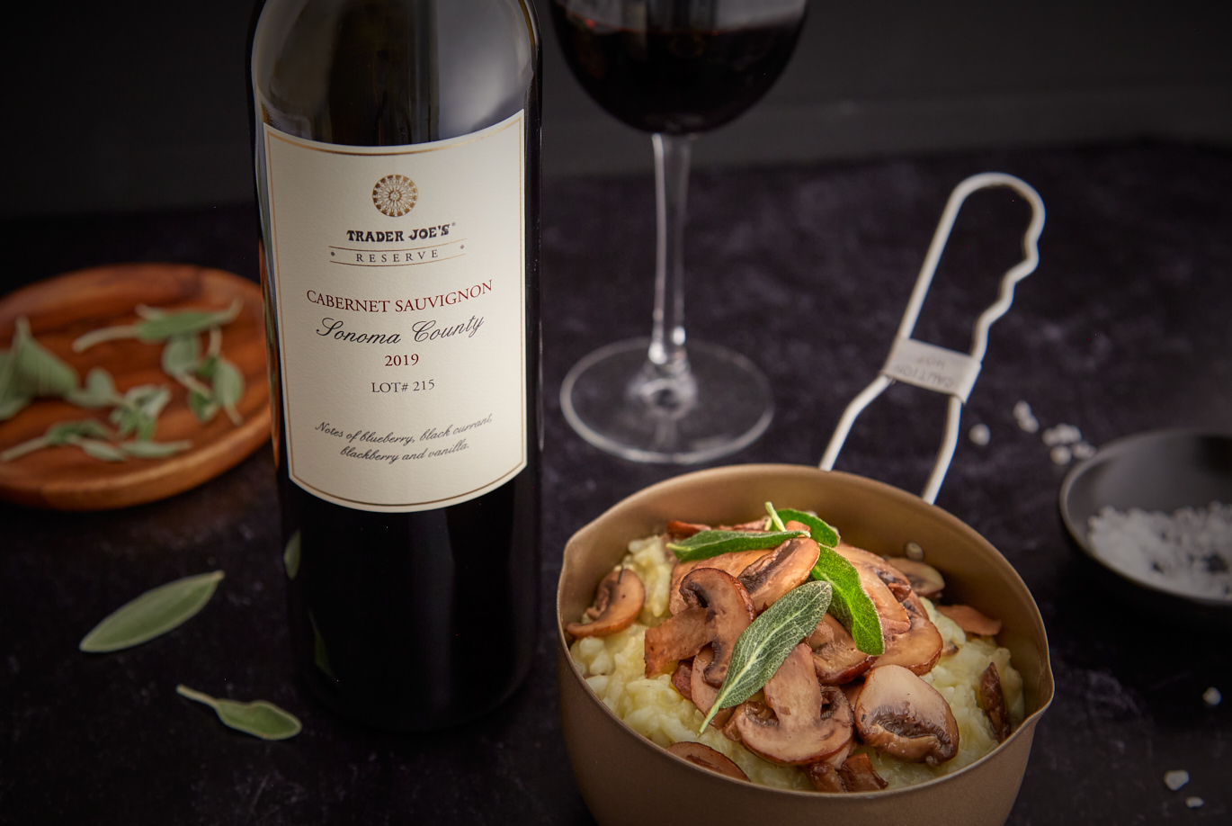 Trader Joe's Reserve Cabernet Sauvignon Sonoma County 2019 Lot 215 bottle and glass of wine next to a small pot with mushroom risottor