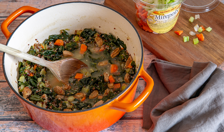 Wooden spoon stirring Spicy Sausage and Kale Soup in an orange stockpot.